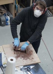 Marsden sanding the bottom paint off the propeller strut.